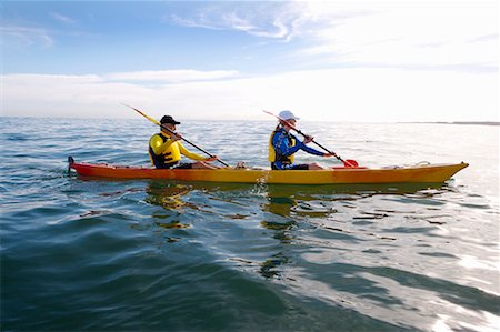 side view of person rowing in boat - Couple canoeing at sea, side view Stock Photo - Premium Royalty-Free, Code: 613-01650731