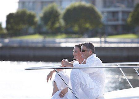 Mature couple sitting on yacht's bow, drinking wine Stock Photo - Premium Royalty-Free, Code: 613-01779710
