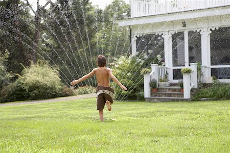 Boy (8-9) running through sprinkler in garden, rear view Stock Photo - Premium Royalty-Free, Code: 613-01829756