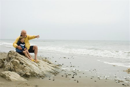 southern california - Senior man with grandson (8-9) sitting on beach Stock Photo - Premium Royalty-Free, Code: 613-02044690