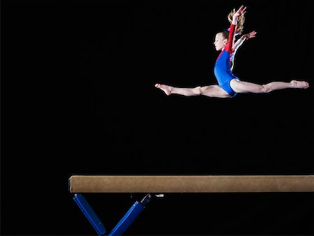 preteen girls gymnastics - Gymnast (9-10) leaping on balance beam Stock Photo - Premium Royalty-Free, Code: 613-02045339