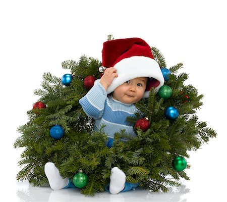 shy baby - Baby boy (6-11 months) wearing Santa hat, sitting in wreath, studio portrait Stock Photo - Premium Royalty-Free, Code: 613-02391574