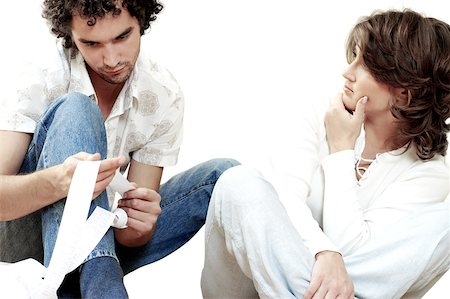Young man sitting with a young woman holding a receipt Stock Photo - Premium Royalty-Free, Code: 625-00836408