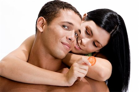 Young woman holding a condom embracing a young man from behind Stock Photo - Premium Royalty-Free, Code: 625-00837636