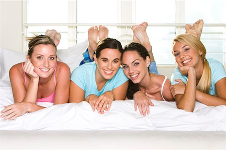 Portrait of four young women lying down side by side on a bed Stock Photo - Premium Royalty-Free, Code: 625-00839049