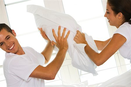 student fighting - Side profile of a young couple having a pillow fight Stock Photo - Premium Royalty-Free, Code: 625-00839074