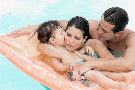 people kissing little boys - Parents with their son in a swimming pool Stock Photo - Premium Royalty-Free, Code: 625-00849154