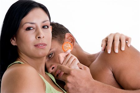 Portrait of a young couple embracing each other holding a condom Stock Photo - Premium Royalty-Free, Code: 625-00841272