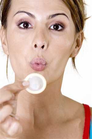 Portrait of a mid adult woman blowing a condom Stock Photo - Premium Royalty-Free, Code: 625-00841353
