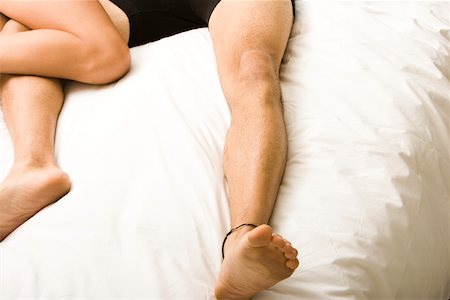 Low section view of a young couple lying on the bed Stock Photo - Premium Royalty-Free, Code: 625-00843218
