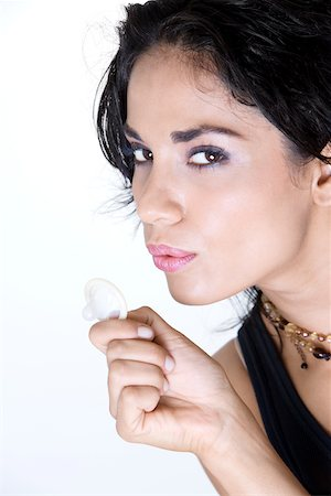 Close-up of a young woman blowing a condom Stock Photo - Premium Royalty-Free, Code: 625-00850027