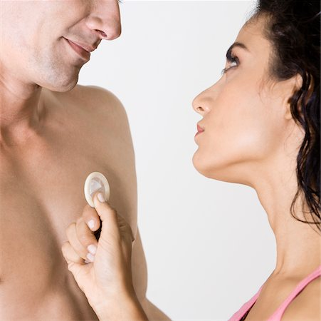 Close-up of a young man and a young woman holding a condom Stock Photo - Premium Royalty-Free, Code: 625-00850079