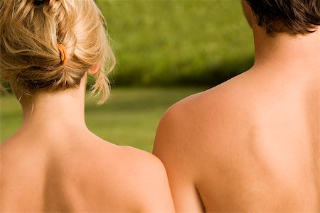 Rear view of a young couple sunbathing in a garden Stock Photo - Premium Royalty-Free, Code: 625-00850097
