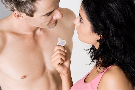 High angle view of a young woman showing a condom to a mid adult man Stock Photo - Premium Royalty-Free, Code: 625-00851404
