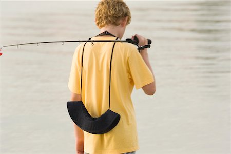 Rear view of a teenage boy holding a fishing rod Stock Photo - Premium Royalty-Free, Code: 625-00899652