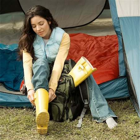 High angle view of a young woman wearing galoshes in a tent Stock Photo - Premium Royalty-Free, Code: 625-00900909
