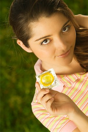 Portrait of a young woman holding a condom Stock Photo - Premium Royalty-Free, Code: 625-00902002