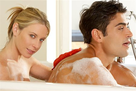 Portrait of a young woman scrubbing a young man's back Stock Photo - Premium Royalty-Free, Code: 625-00902133