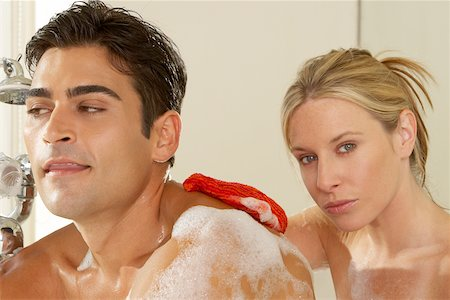 Close-up of a young woman scrubbing a young man's back with a bath sponge Stock Photo - Premium Royalty-Free, Code: 625-00902254