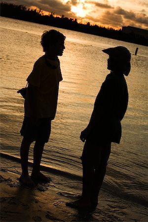 Silhouette of two boys standing on the beach Stock Photo - Premium Royalty-Free, Code: 625-00902770