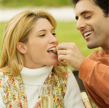 Mid adult man feeding grapes to a young woman Stock Photo - Premium Royalty-Free, Code: 625-01039209