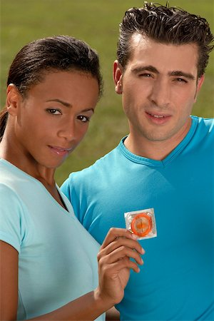 Portrait of a young woman holding a condom with a mid adult man standing beside her Stock Photo - Premium Royalty-Free, Code: 625-01039530