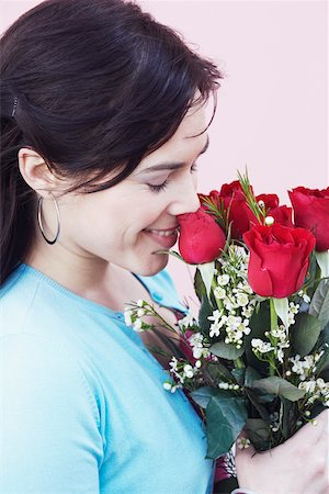 Close-up of a young woman smelling a bunch of roses Stock Photo - Premium Royalty-Free, Code: 625-01096543