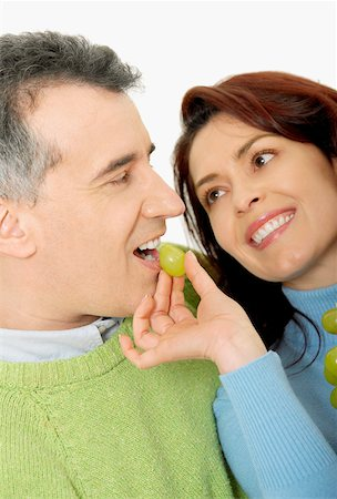 Close-up of a mid adult woman feeding a grape to a mid adult man Stock Photo - Premium Royalty-Free, Code: 625-01097431
