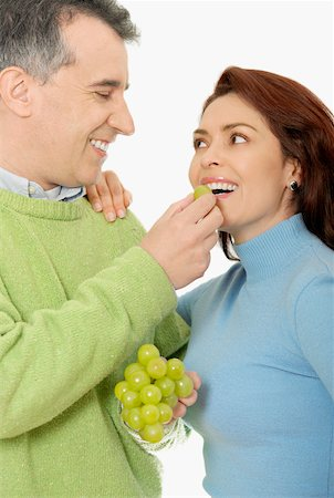 Close-up of a mid adult man feeding a grape to a mid adult woman Stock Photo - Premium Royalty-Free, Code: 625-01097445