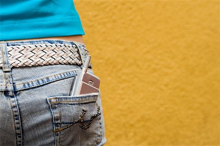 Close-up of a mobile phone in a teenage girl's back pocket Stock Photo - Premium Royalty-Free, Code: 625-01093686