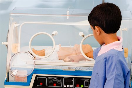 Close-up of a boy touching a baby boy in an incubator Stock Photo - Premium Royalty-Free, Code: 625-01249582