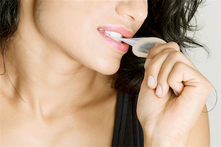 Close-up of a young woman biting a condom Stock Photo - Premium Royalty-Free, Code: 625-01252359