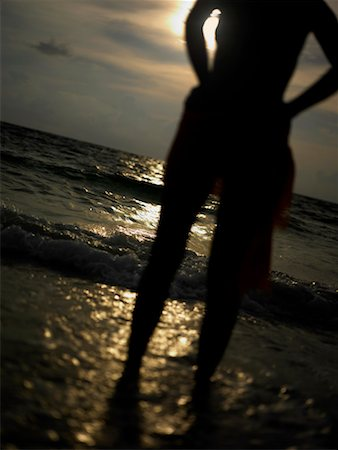 Silhouette of a young woman standing on the beach Stock Photo - Premium Royalty-Free, Code: 625-01260730