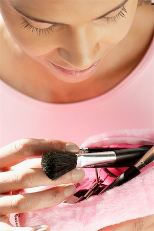 Close-up of a young woman taking make-up brushes from her purse Stock Photo - Premium Royalty-Free, Code: 625-01261539