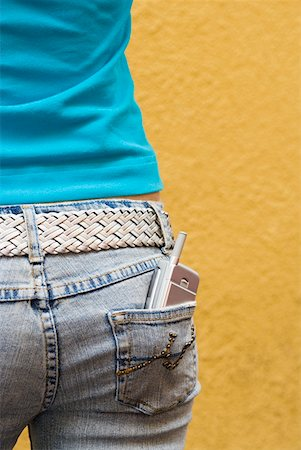 Close-up of a mobile phone in a teenage girl's back pocket Stock Photo - Premium Royalty-Free, Code: 625-01261781