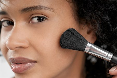 Portrait of a young woman applying blush with a brush Stock Photo - Premium Royalty-Free, Code: 625-01263069