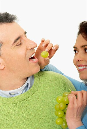 Close-up of a mid adult woman feeding a grape to a mid adult man Stock Photo - Premium Royalty-Free, Code: 625-01263220