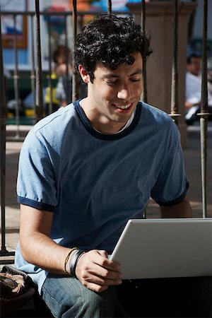 Close-up of a young man using a laptop and smiling Stock Photo - Premium Royalty-Free, Code: 625-01746699