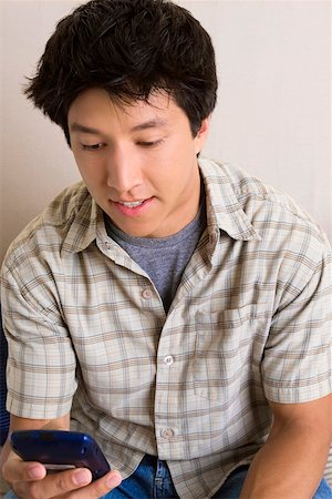 Close-up of a young man holding a mobile phone and text messaging Stock Photo - Premium Royalty-Free, Code: 625-01746908
