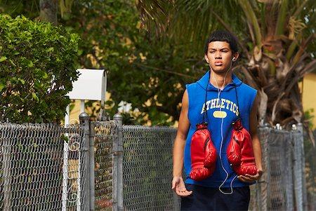Teenage boy listening an ipod and walking Stock Photo - Premium Royalty-Free, Code: 625-01747073