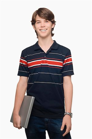 Portrait of a teenage boy holding a laptop and smiling Stock Photo - Premium Royalty-Free, Code: 625-01747349