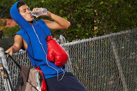 Side profile of a teenage boy listening an ipod and drinking water from a bottle Stock Photo - Premium Royalty-Free, Code: 625-01747720