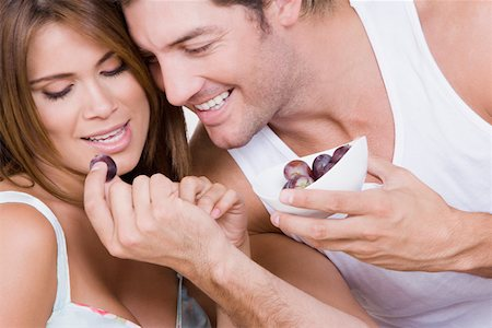 Mid adult man feeding grapes to a young woman and smiling Stock Photo - Premium Royalty-Free, Code: 625-01748647