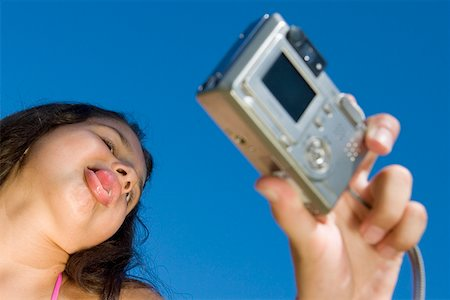 Low angle view of a girl taking a photograph of herself Stock Photo - Premium Royalty-Free, Code: 625-01748693