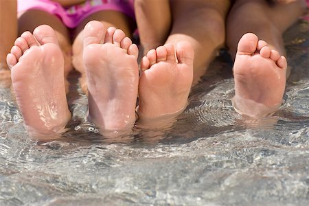 Low section view of two girls sitting in water Stock Photo - Premium Royalty-Free, Code: 625-01748899