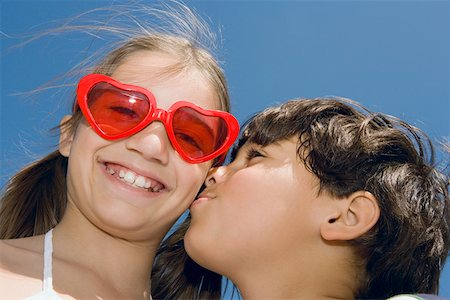 preteen kissing - Low angle view of a boy kissing a girl Stock Photo - Premium Royalty-Free, Code: 625-01749035