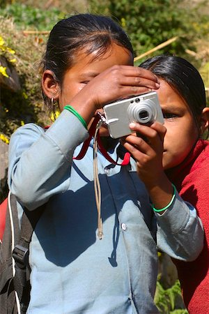 Close-up of two girls taking a photograph of themselves, Tadapani, Annapurna Range, Himalayas, Nepal Stock Photo - Premium Royalty-Free, Code: 625-01752943