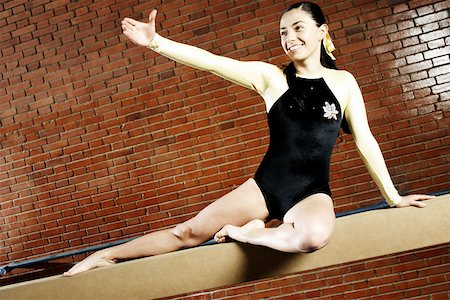 Female gymnast practicing on a balance beam and smiling Stock Photo - Premium Royalty-Free, Code: 625-02266419