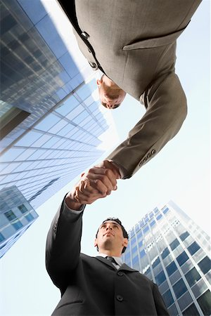 Low angle view of two businessmen shaking hands Stock Photo - Premium Royalty-Free, Code: 625-02266564