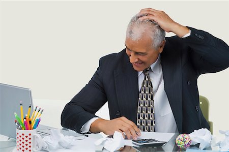 Businessman sitting at a desk in an office and smiling Stock Photo - Premium Royalty-Free, Code: 625-02267003